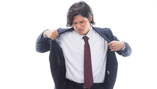 自分の体臭でしかめ面するスーツ姿の男