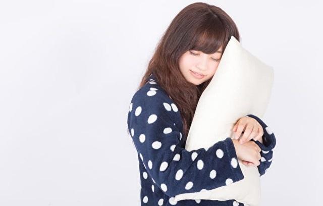枕に抱き着いて寝ている女性