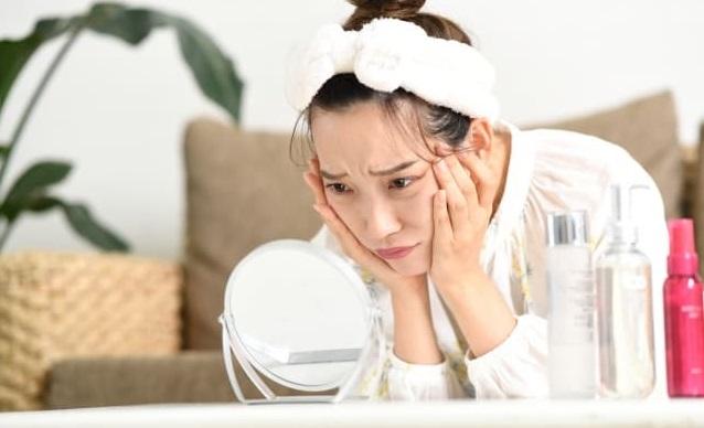 自分の顔を鏡で悩んでいる表情をしている女性